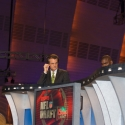 Mel Kiper, Jr. picks his ear or adjusts an ear piece or does something to that magical coif of a hair helmet!